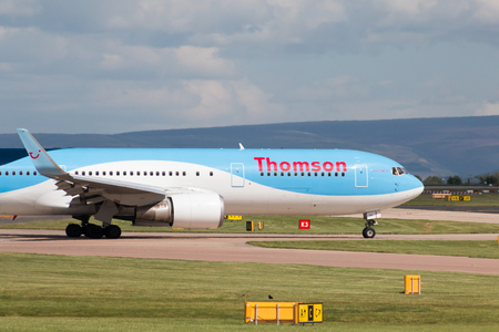 Thomson Airways Boeing 767 wide-body passenger plane G-OBYH taxiing on Manchester International Airport taxiway.