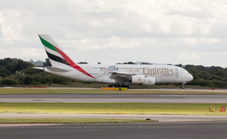 Emirates Airbus A380 double-decker wide-body passenger plane taking off from Manchester International Airport taxiway.