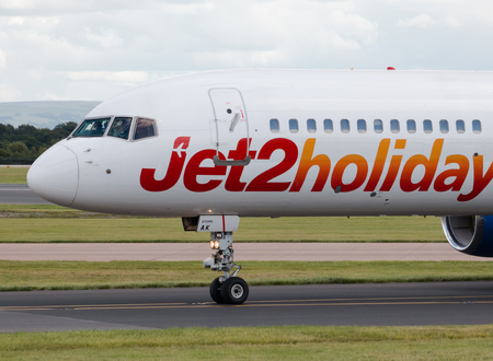 holiday budget: Jet2 Holidays Boeing 757 narrow-body passenger plane taxiing on Manchester International Airport taxiway after landing.