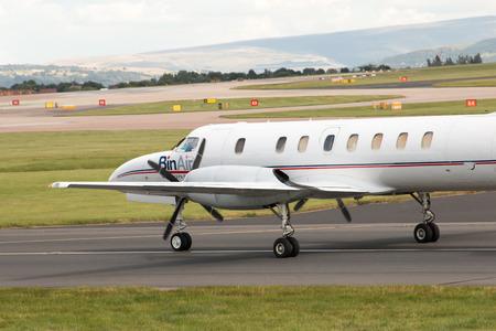 turboprop: BinAir Fairchild Swearingen Metroliner turboprop passenger plane taxiing on Manchester International Airport taxiway after landing. Editorial