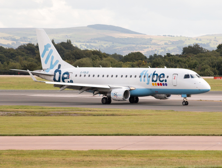medium body: Flybe Embraer ERJ-175 narrow-body medium-range passenger plane G-FBJD taxiing on Manchester International Airport taxiway after landing. Editorial