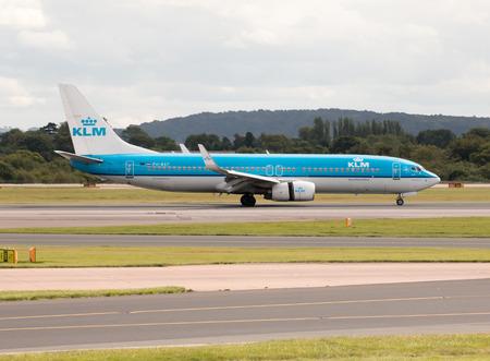 klm: KLM Royal Dutch Airlines Boeing 737 narrow-body passenger plane PH-BXF landing to Manchester International Airport runway.
