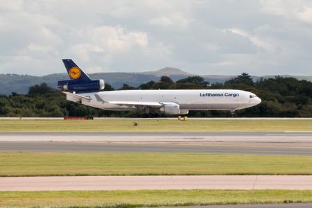 taking off: Lufthansa Cargo MD-11 three-engine wide-body cargo plane taking off from Manchester International Airport runway.