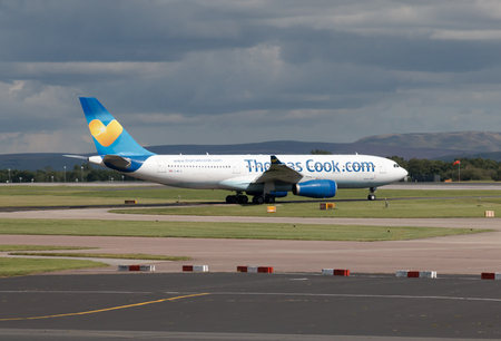airbus: Thomas Cook Airbus A330 wide-body passenger plane taxiing on Manchester International Airport tarmac. Editorial