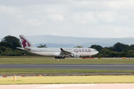 departing: Qatar Airways A330 wide-body passenger plane departing from Manchester International Airport runway.