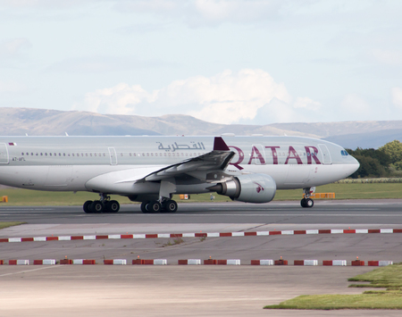 departing: Qatar Airways A330 wide-body passenger plane departing from Manchester International Airport runway.