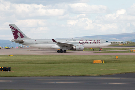airways: Qatar Airways A330 wide-body passenger plane taxiing on Manchester International Airport tarmac before departure.