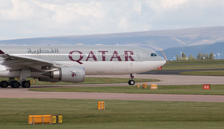 twin engine: Qatar Airways A330 wide-body passenger plane taxiing on Manchester International Airport tarmac before departure.
