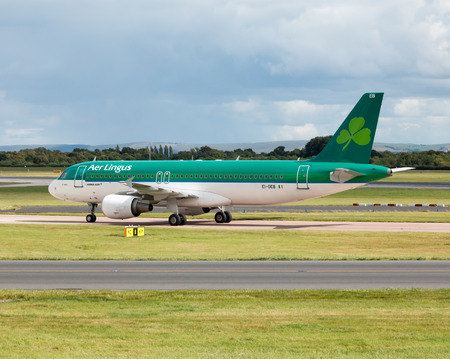 jet plane: Aer Lingus Airbus A320 narrow-body passenger plane EI-DEB, St. Nathy taxiing on Manchester International Airport tarmac after landing. Editorial