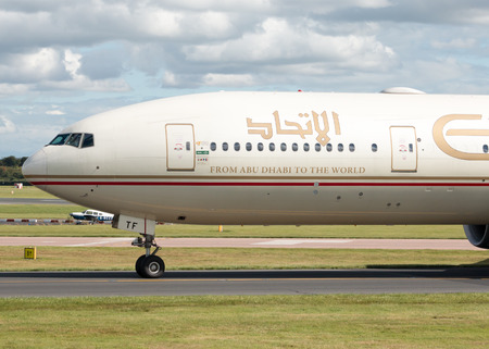 boeing: Etihad Airways Boeing 777 wide-body passenger plane A6-ETF taxiing on Manchester International Airport tarmac after landing.
