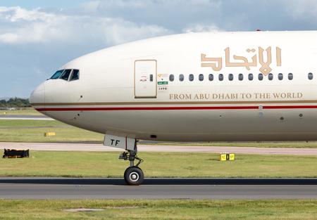 airways: Etihad Airways Boeing 777 wide-body passenger plane A6-ETF taxiing on Manchester International Airport tarmac after landing.