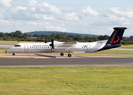 turboprop: Brussels Airlines Bombardier Dash 8 Q400 regional turboprop passenger plane G-ECOK taxiing on Manchester International Airport tarmac after landing. Editorial