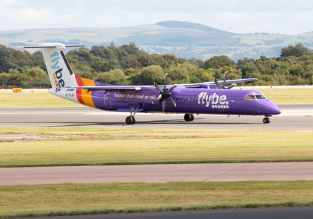 livery: Flybe Bombardier Dash 8 Q400 regional passenger plane G-FLBC, purple Flybe livery taxiing on Manchester International Airport tarmac after landing Editorial