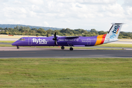 bombardier: Flybe Bombardier Dash 8 Q400 regional passenger plane G-FLBC, purple Flybe livery taxiing on Manchester International Airport tarmac after landing Editorial