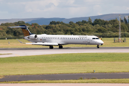 airborne vehicle: Eurowings Bombardier CRJ900 NextGen passenger plane taxiing on Manchester International Airport after landing.