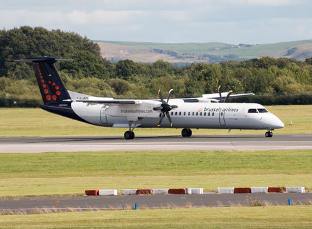 regional: Brussels Airlines Bombardier Dash 8 Q400 regional turboprop passenger plane taxiing on Manchester International Airport tarmac after landing.