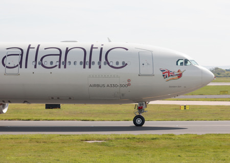 virgin girl: Virgin Atlantic Airbus A330-300 wide-body passenger plane (G-VGBR, Golden Girl) taxiing on Manchester International Airport tarmac. Editorial