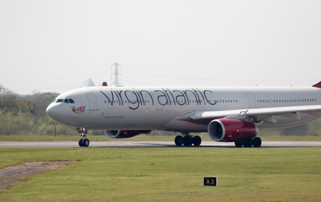 virgin girl: Virgin Atlantic Airbus A330-300 wide-body passenger plane (G-VGBR, Golden Girl) departing from Manchester International Airport runway.