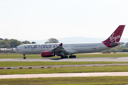departing: Virgin Atlantic Airbus A330-300 wide-body passenger plane (G-VGBR, Golden Girl) departing from Manchester International Airport runway.