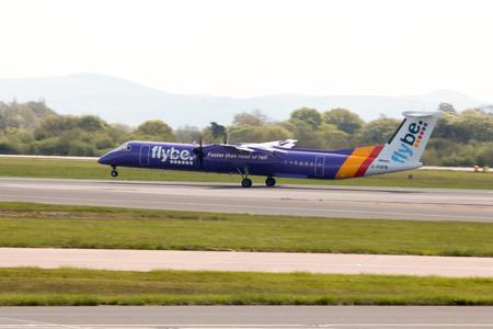 turboprop: Flybe Bombardier Dash 8 Q400 twin-engine, medium range, turboprop passenger plane (G-PRPB) landing to Manchester International Airport runway. Editorial
