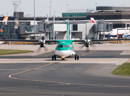 turboprop: Aer Lingus ATR 72-600 twin-engine turboprop short-haul regional passenger plane (EI-FAT) taxiing on Manchester International Airport tarmac.