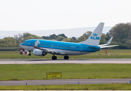 KLM Boeing 737-7K2(WL) narrow-body passenger plane (PH-BGM, Cormorant) taking off from Manchester International Airport runway.