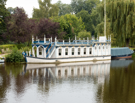 river boat: Beautiful river boat on the banks of River Thames, viewed from the High Street of Streatley, Berkshire, England. Overcast weather.