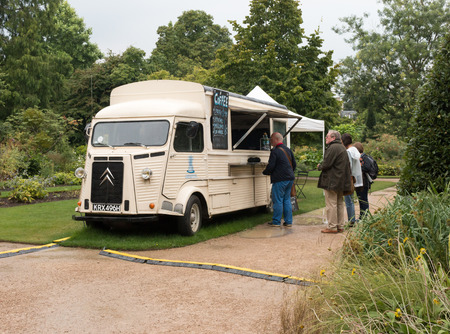oxfordshire: Coffee van in Oxford University Botanic Garden. Overcast weather with light rain. People queuing for coffee.