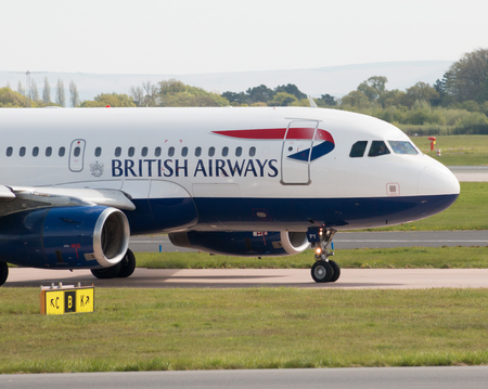 British Airways Airbus A319-131 narrow-body passenger plane (G-EUPY) taxiing on Manchester International Airport tarmac.