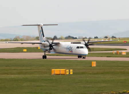turboprop: Flybe Bombardier Dash 8 Q400 twin-engine, medium range, turboprop passenger plane (G-JECN) taxiing on Manchester International Airport tarmac.