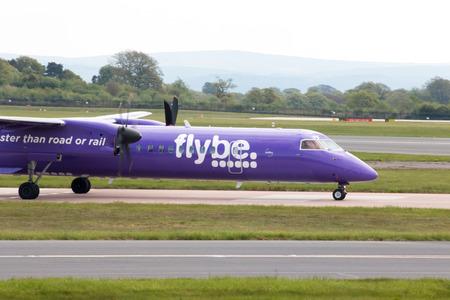 turboprop: Flybe Bombardier Dash 8 Q400 twin-engine, medium range, turboprop passenger plane taxiing on Manchester International Airport tarmac.