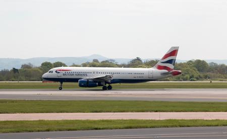 British Airways Airbus A320-232 narrow-body passenger plane (G-EUYF) landing to Manchester International Airport runway.