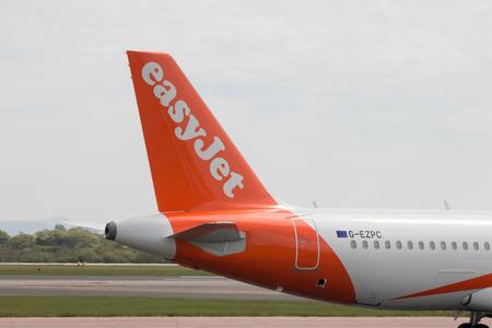 stabilizer: easyJet A320-214 narrow-body passenger plane (G-EZPC) vertical stabilizer, Manchester International Airport tarmac.