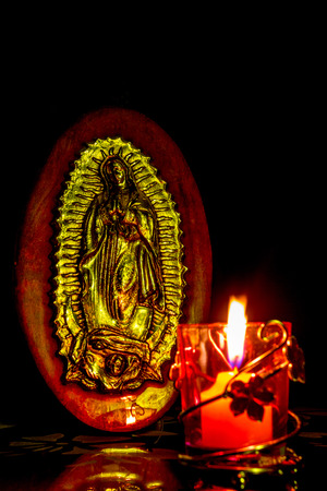 The Virgins image of Guadalupe carved on a wood illuminated with the candlelight on a black background