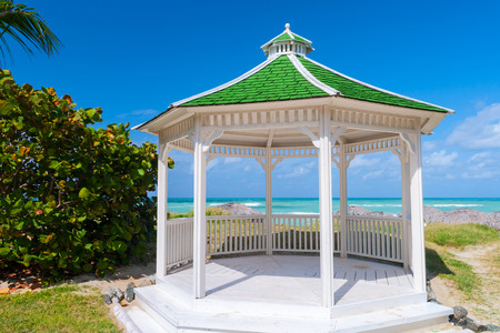 A gazebo or pavilion with hexagonal shape, isolated, with a green roof and opened by all the sides