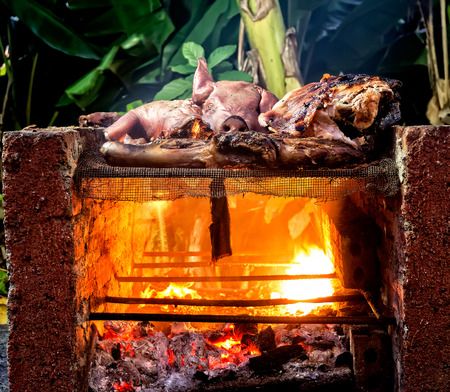 Charcoal-grilled pig in a native fireplace Stock Photo