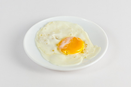 Fried hen egg in a white dish
