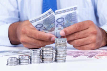 Organized groups of coins in ascending order. A man manipulating money in background Stock Photo