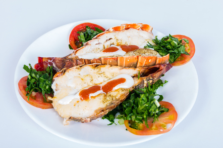 Two grilled lobster , served on a plate decorated with tomato and spinach Stock Photo