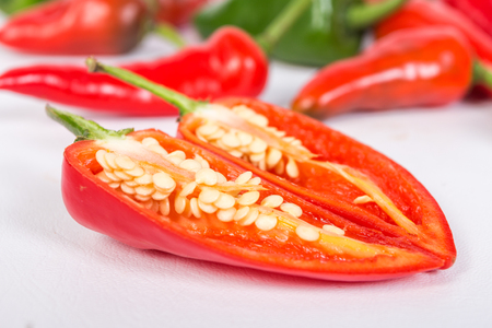 Two halves of a pepper with seeds in the foreground and a group of peppers in the background desnfocados