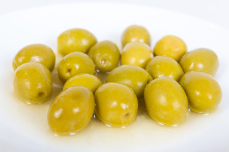 A group of olives on white plate