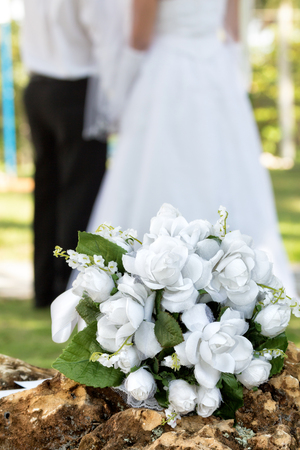 white bouquet on a rock and the couple in the background