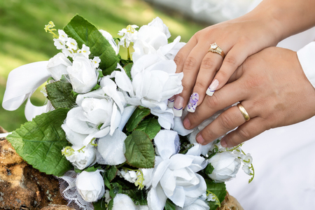 white bouquet on a rock and grooms hands one over the other with their wedding rings since