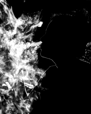 A woman silhouette surround by cigar smoke getting out from her nose. Stock Photo