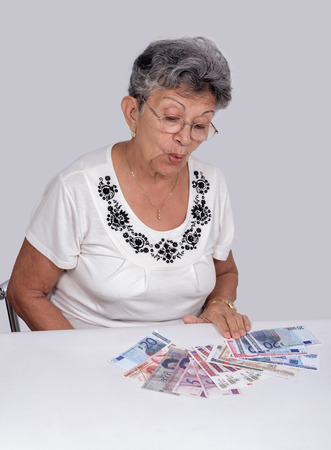 An old woman wearing glasses with money on the desk