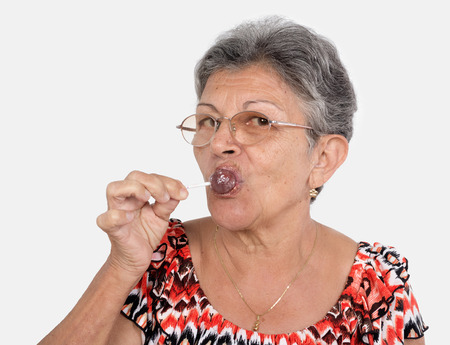 An old woman wearing glasses with a candy in her mouse