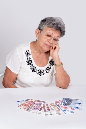 An old woman wearing glasses looking money