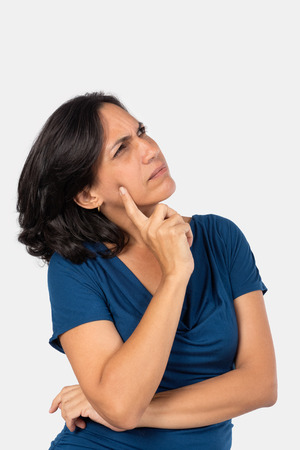 A woman thinking,with one finger touching her face, she is wearing a blue blouse