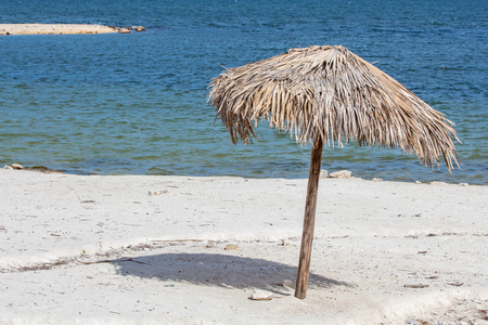 Isolated wooden umbrella in the sand