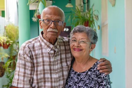 An smiling elderly couple, both wearing glasses.